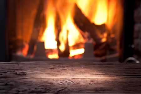 Old wooden table in front of the fireplace. Stock Photo - 24310441