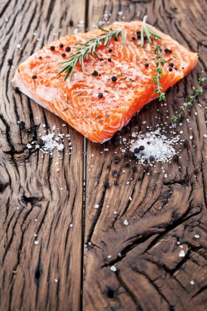 Salmon filet with spices on a wooden carving board. Macro shot. photo