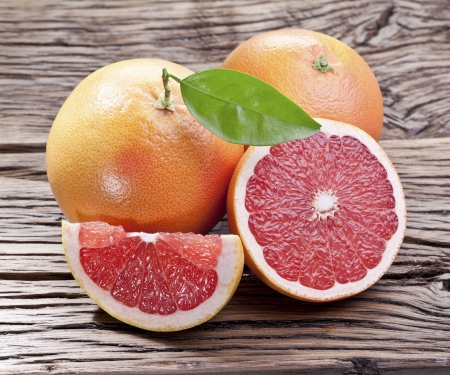 grapefruits: Grapefruits with leaf on a wooden table.