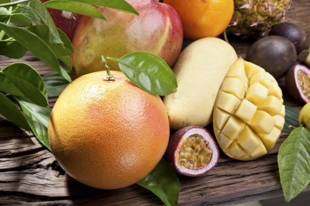 exotic fruits: Exotic fruits on a wooden table with green foliage on the background. Stock Photo