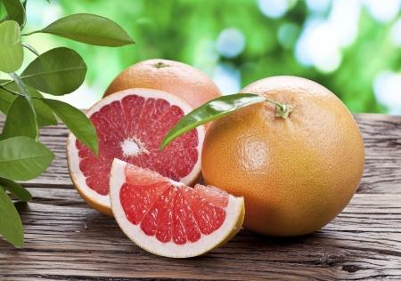 Grapefruits auf einem Holztisch mit grünen Blättern auf den Hintergrund.