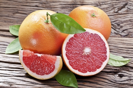 orange cut: Grapefruits with leaves on a wooden table.