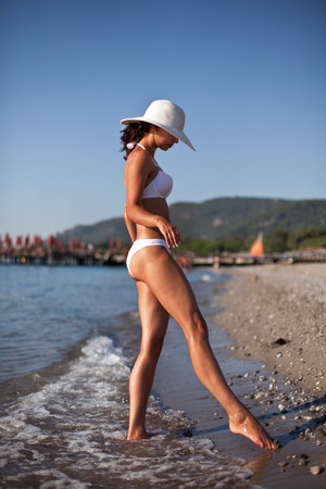 Young woman in white swimsuit sunbathering at the seaside. photo