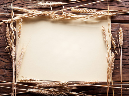 Ears of wheat in the form frame on old wooden table. photo