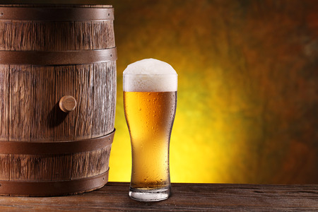 near beer: The glass of beer near old woden barrel. Stock Photo