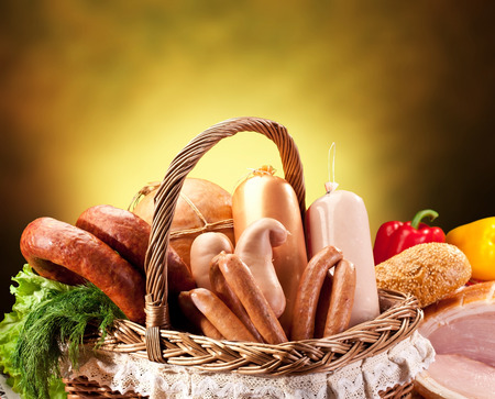 meat counter: Variety of sausage products in the basket over brown background. Close-up shot.