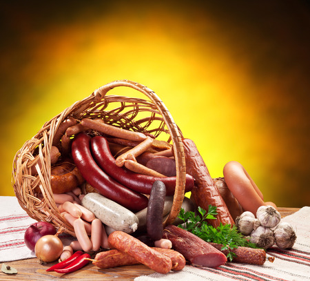 processed: Variety of sausage products in the basket on the wooden table.