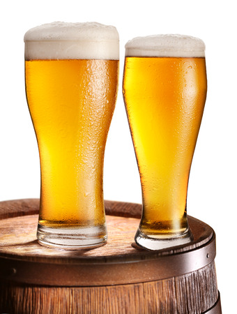 woden: Two glasses of beer over woden barrel. File contains clipping paths.