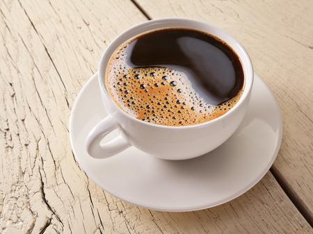filiżanka kawy: Filiżanka kawy na starym białym drewnianym stole.