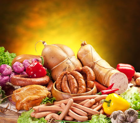 processed: Still-life with sausage products, vegetables and herbs on a yellow-brown background.