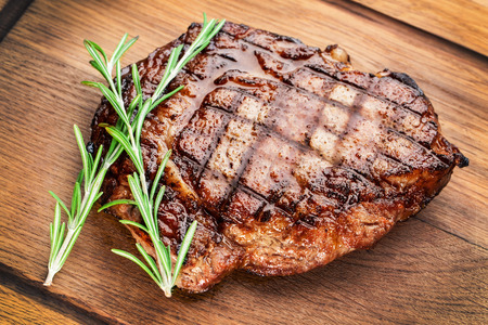 Beef steak with rosemary on a wooden table. Stock fotó