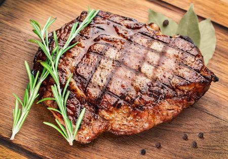 木製のテーブルにローズマリーと牛ステーキ。