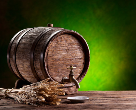 oak barrel: Old oak barrel on a wooden table. Behind blurred green background. Stock Photo