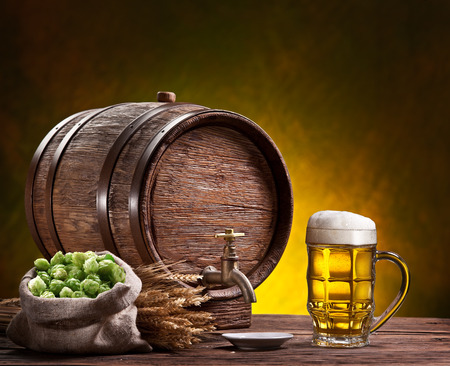 beer barrel: Beer glass, old oak barrel and wheat ears on wooden table. Stock Photo