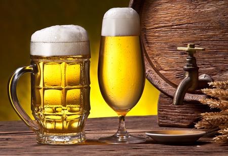 oak barrel: Beer glasses, old oak barrel and wheat ears on wooden table.