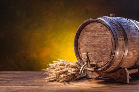 keg: Old oak barrel on a wooden table. Behind blurred dark background.