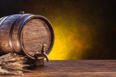 木製のテーブルに古いオーク材の樽。後ろには、暗い背景がぼやけています。