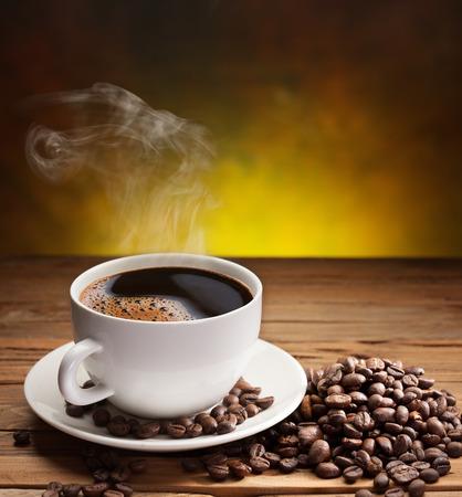 Tasse Kaffee mit Kaffeebohnen in der Nähe auf alten Holztisch. Standard-Bild - 27359779