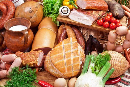 processed: Variety of sausage products with vegetables and herbs. Close-up shot. Stock Photo