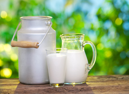 glass of milk: Milk in various dishes on the old wooden table in an outdoor setting.