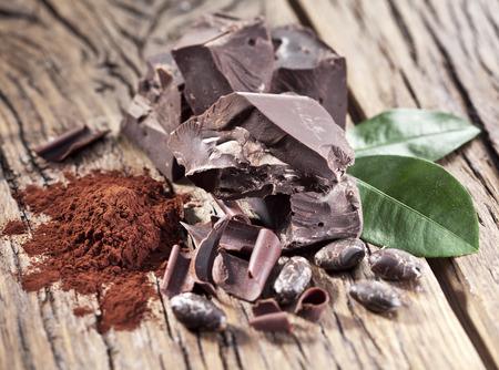 chunk: Chocolate and cocoa bean over wooden table. Stock Photo