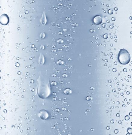 Las gotas de agua sobre fondo de cristal azul.