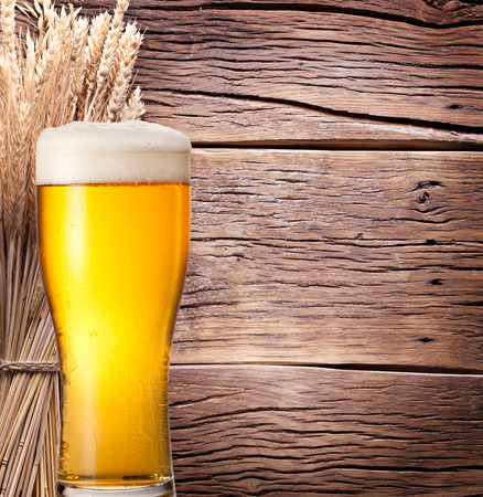 Ears of wheat & beer glass on old wooden table. Stock Photo