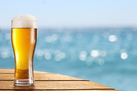 vasos de cerveza: Cerveza de cristal sobre un fondo borroso de la mar.