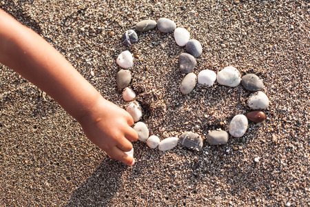 heart in sand: Babys hand making heart of marine shingles on the sand. Stock Photo