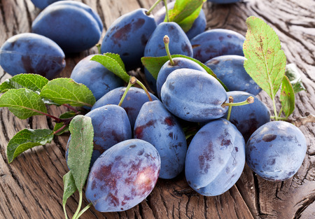purple leaf plum: Plums on an old wooden table in the garden. Stock Photo
