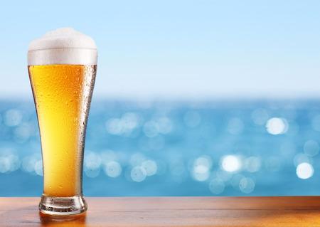 frio: vaso de cerveza fría en la mesa de un bar