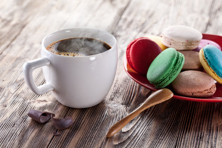 Cup of coffee and french macarons on an old wooden table. Stock Photo