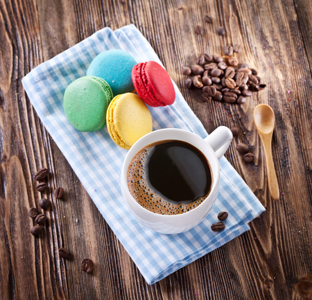 confections: Cup of coffee and french macaron on an old wooden table.