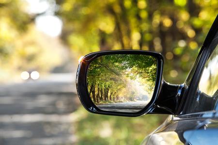 Reflexión del camino soleado de otoño en el mirrow lado del coche.
