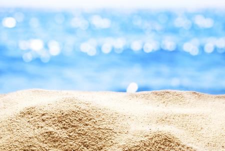 cerrar: Close up de arena con el mar de fondo borroso.