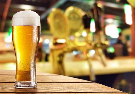 vasos de cerveza: Vaso de cerveza ligera en un bar oscuro.