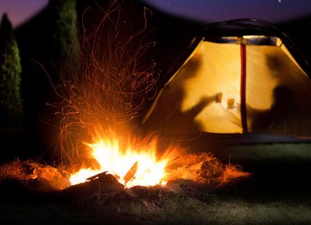Kamp schijnt 's nachts. Het kampvuur in de voorste als het symbool van avontuur en romantisch. Stockfoto