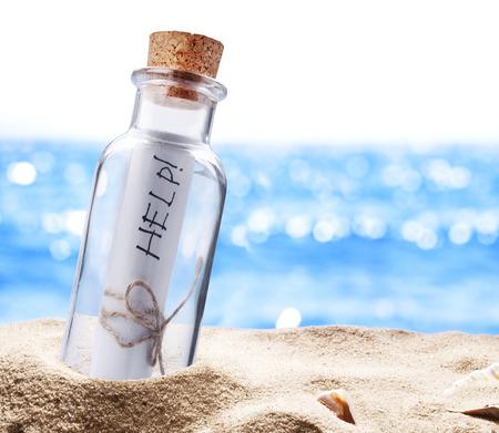 arena: Botella con un mensaje en busca de ayuda. Playa del mar. Foto de archivo