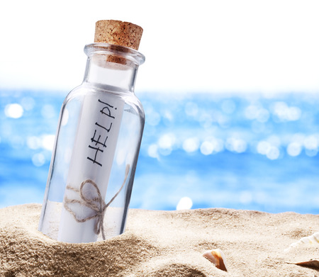 Bottle with a message for help. Sea beach. photo