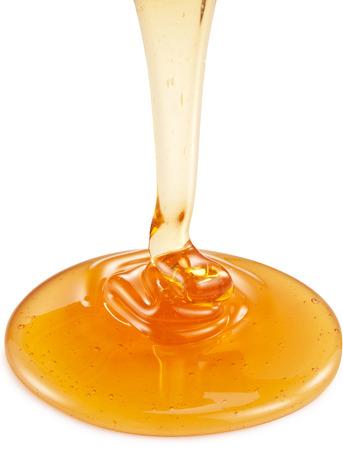 La miel que fluye de palo de madera sobre fondo blanco. Caminos de recortes.