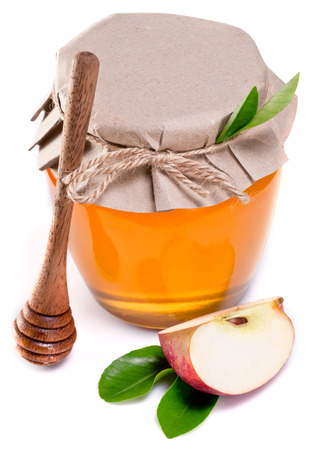 honey apple: Glass can full of honey, piece of apple and wooden dripper over white.