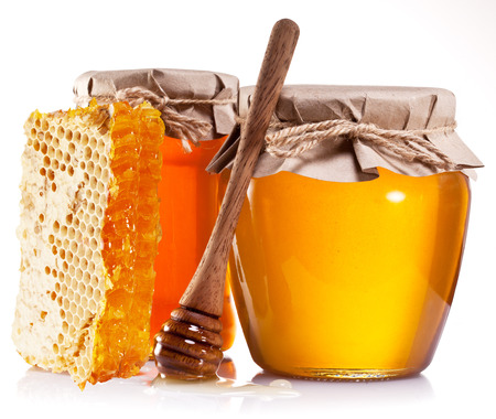 apple honey: Glass cans full of honey, honeycombs and wooden stick on white background.