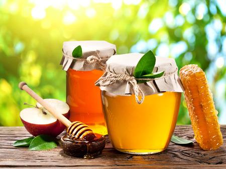 Latas de vidrio lleno de miel, manzanas y peines en la vieja mesa de madera en el jardín.