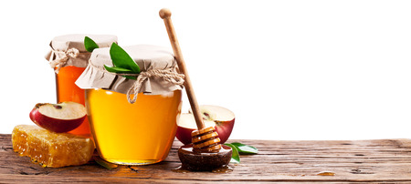 healthy path: Glass can full of honey, apples and honeycombs on old wooden table. Clipping paths.