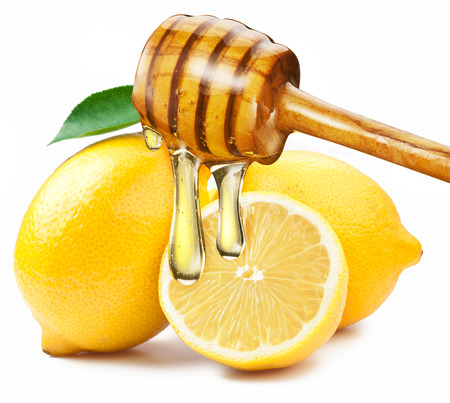 cold remedy: Honey with wood stick pouring onto a slice of lemon. White background. Stock Photo
