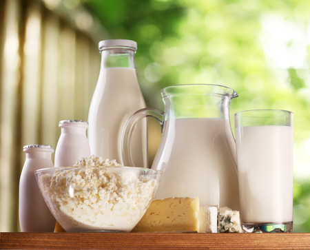 古い木製のテーブルの上の乳製品。背景に農村の背景をぼかします。 写真素材