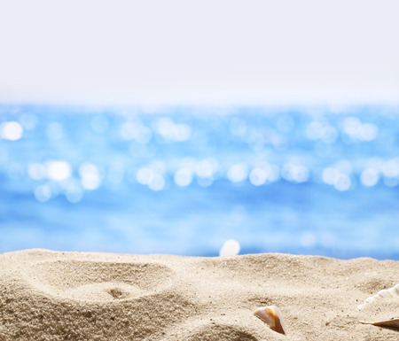 sunny beach: Sand with blurred sea background. File has clipping path for holes in the sand. You can insert the bottle or glass.