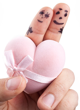 devotions: Couple painted on mans fingers and gift box in the form of heart. Stock Photo