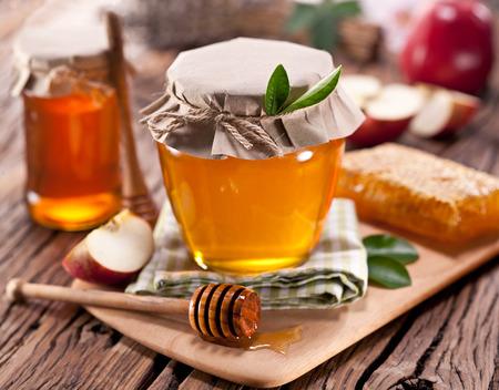 Glasdosen voll Honig, Äpfel Waben auf alten Holztisch. Standard-Bild - 35572921