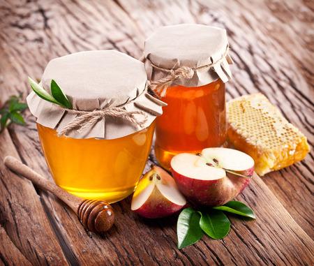 Glasdosen voll Honig, Äpfel und Kämme auf alten Holztisch. Standard-Bild - 35572922